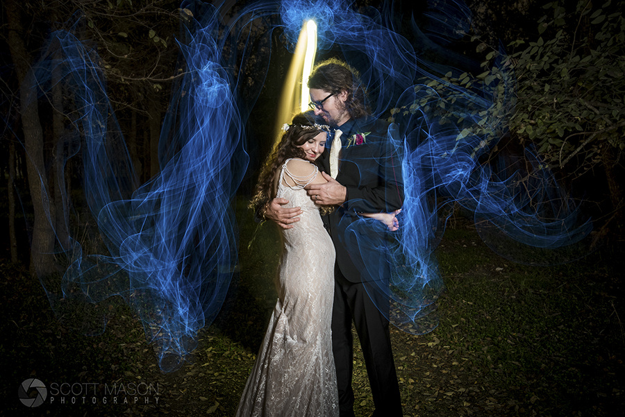 a wedding couple in the woods at night with blue lights surrounding them