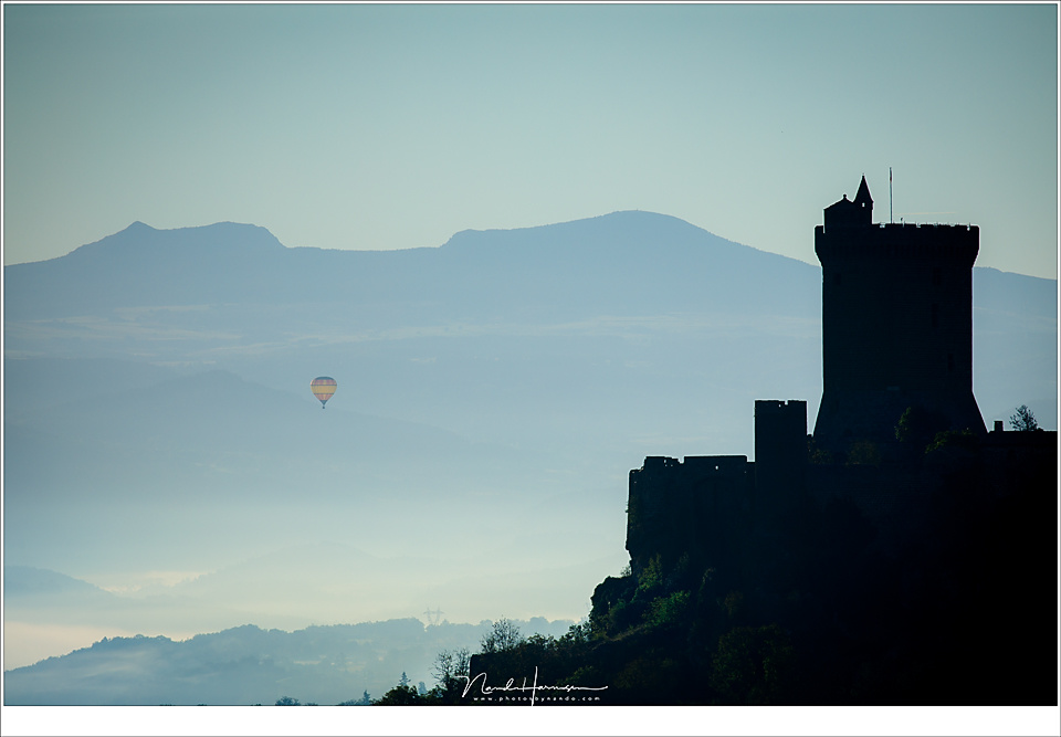 Reality or manipulation?  I took this telelens photo from a hill in the French Auvergne region right after sunrise. The balloon drifted in the distance behind the castle. It is reality.