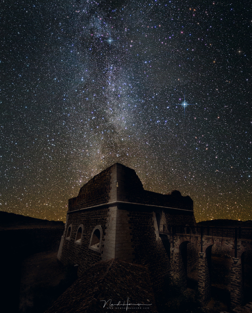 Reality or manipulation?  I photographed this fortress during a summer holiday in broad daylight. I transformed it into a night scenery, and added a Milky Way photo I made somewhere else. As a matter of fact, the image is facing North, away from  the cent