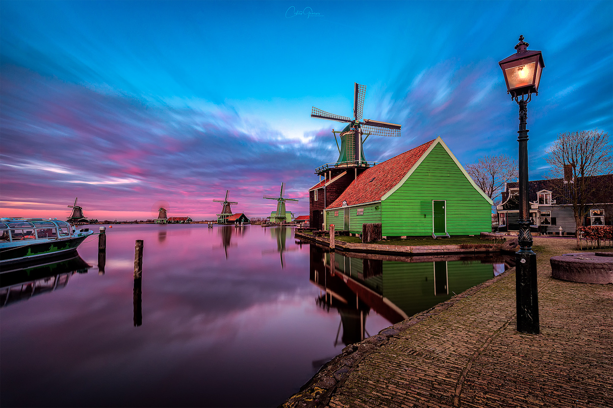 Colorful sunset at the windmill village by Costas Ganasos