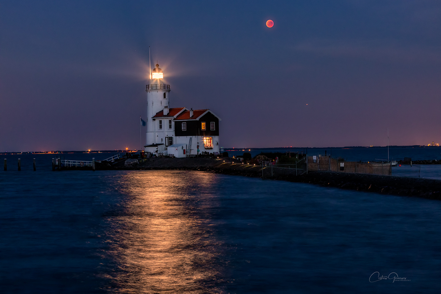 Moon eclipse with Mars, by the lighthouse by Costas Ganasos