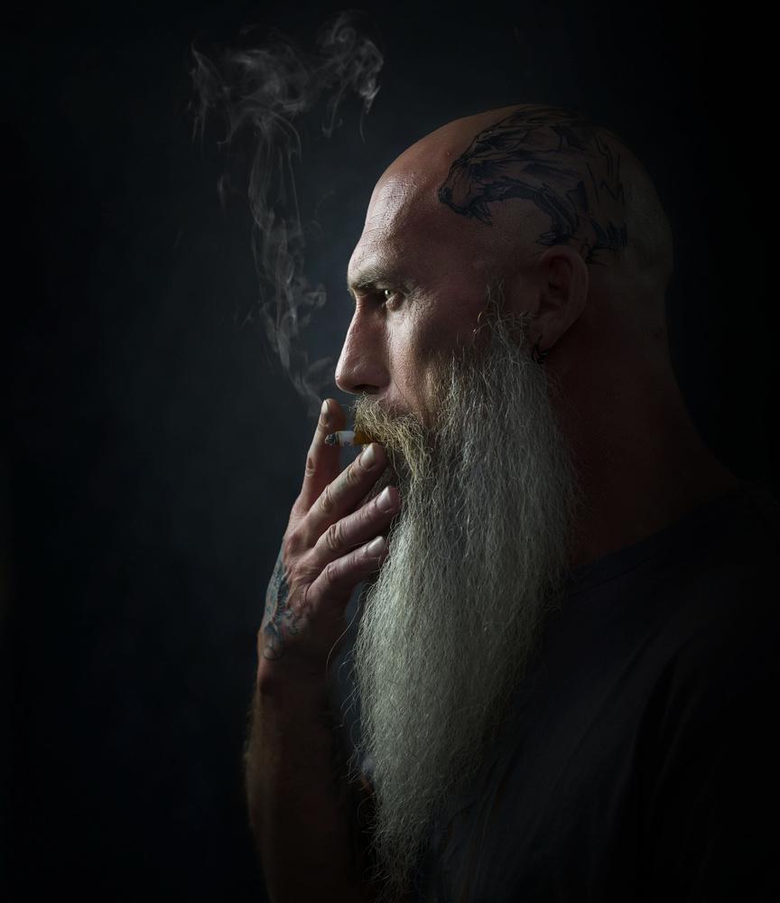Tattooed smoker by John Ohle
