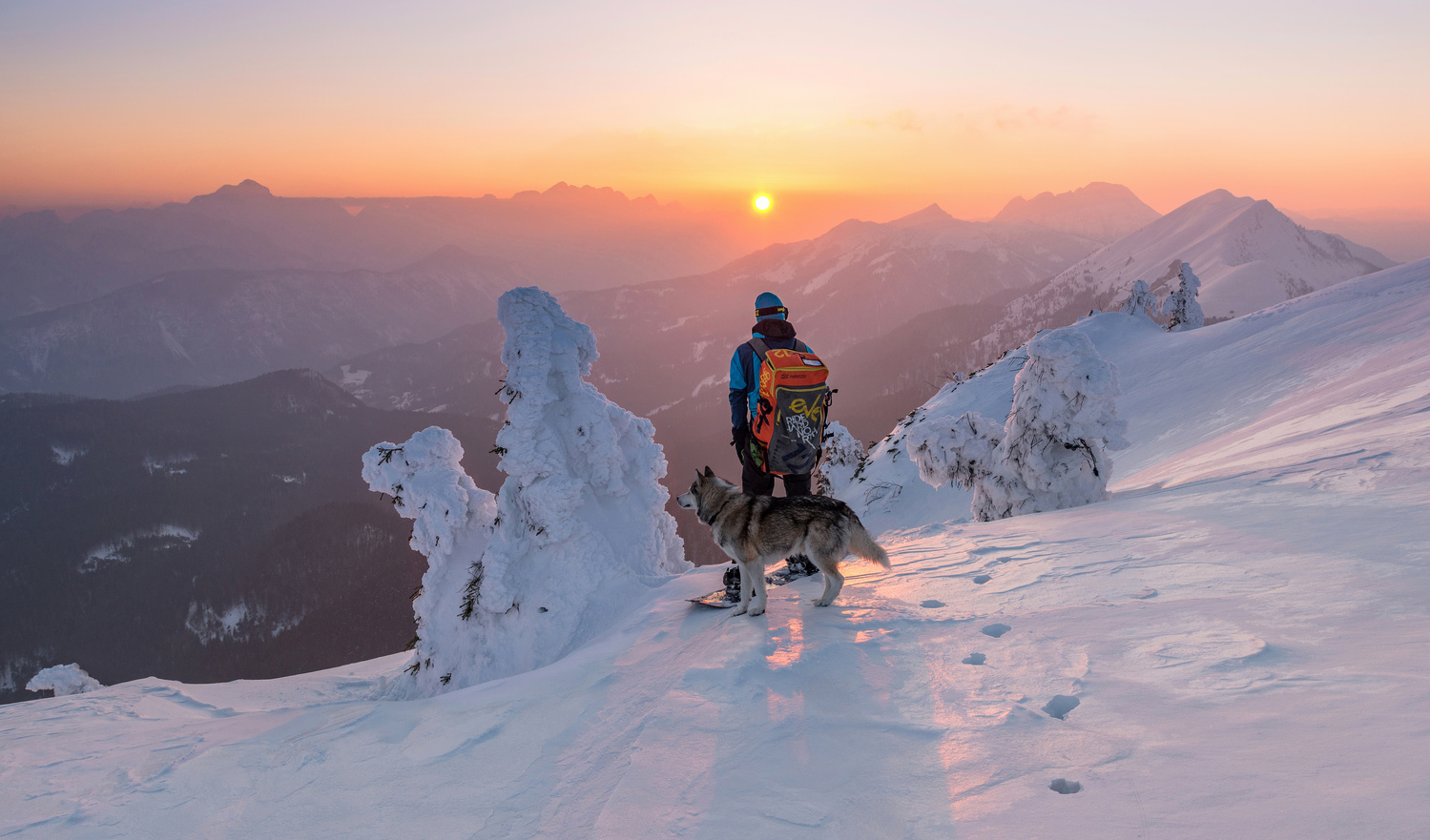 Snowboarder and his dog by Ales Krivec