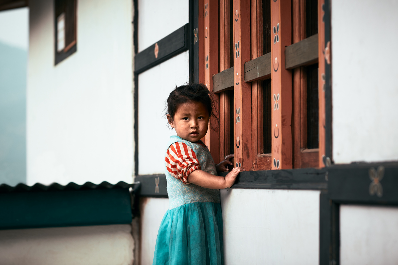 Bhutan: Farmhouse Window and Girl. by Sebastian Leonhardt
