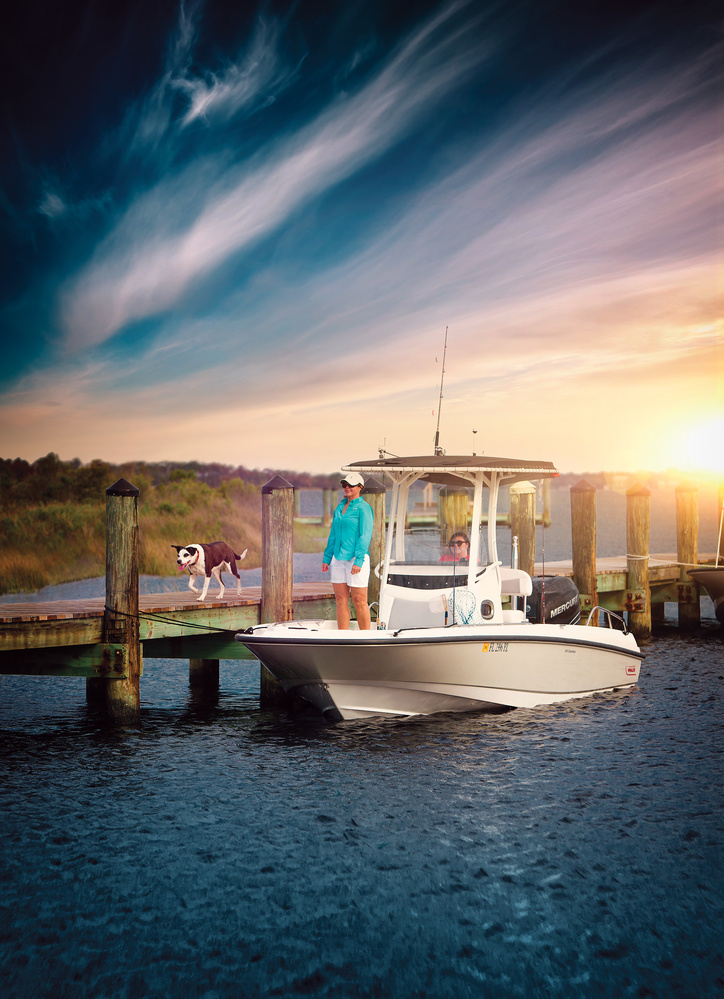 Dog on dock with boat in Fort Meyers, FL by Mike Calabro