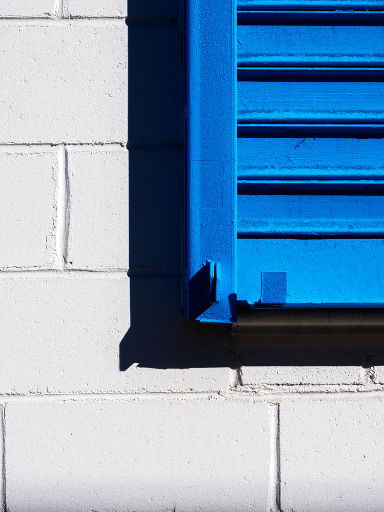 Close up blue shutter on a white wall by Ryan Giglio