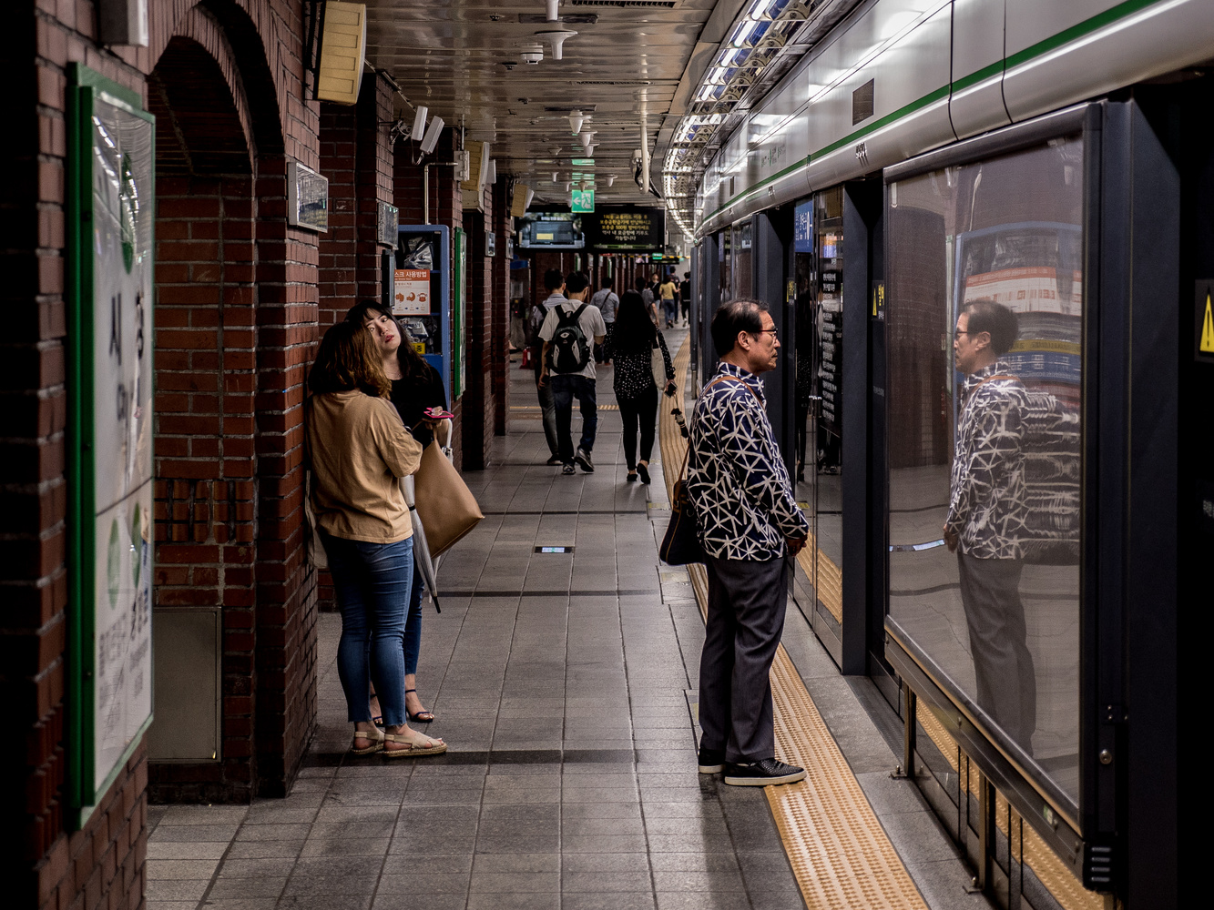 Old man and his reflection waiting for the metro by Isai Oswald