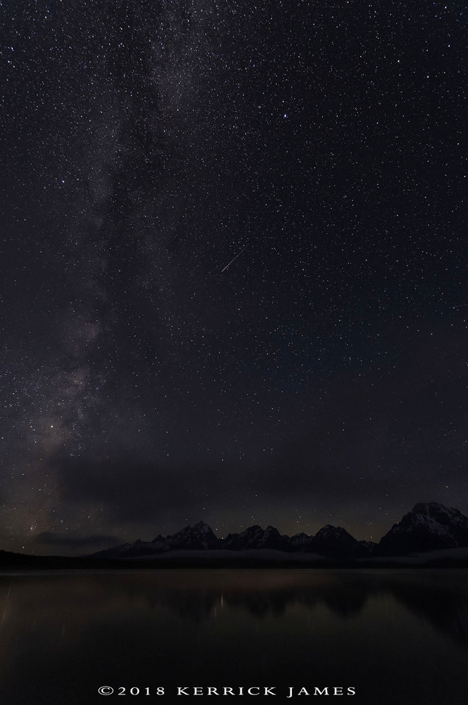 The Milky Way and a meteor above Jackson Lake, Grand Teton NP, Wyoming by Kerrick James