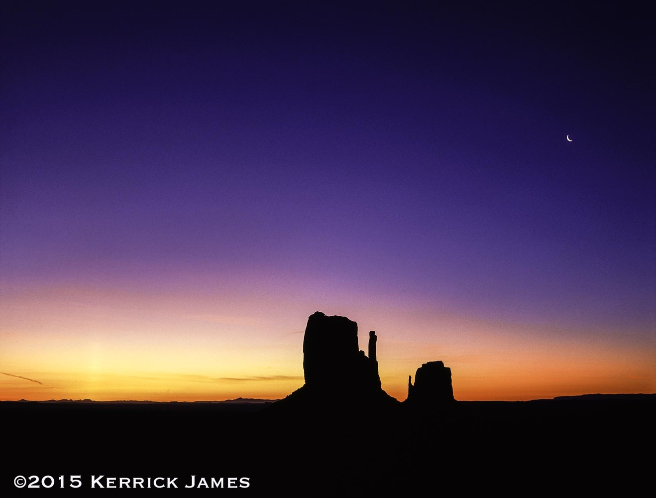 Predawn glow over the Mittens, Monument Valley, Arizona by Kerrick James