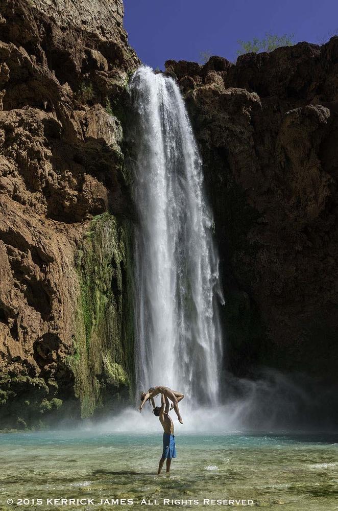 A couple exults under Mooney Falls, Havasupai Reservation, Grand Canyon, Arizona by Kerrick James