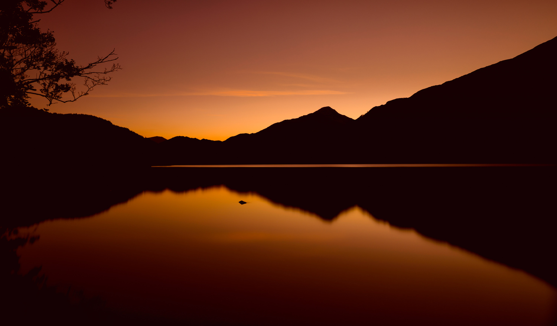 Mountains Reflected in Llyn Gwynant under a burnt orange sky by Will Dale