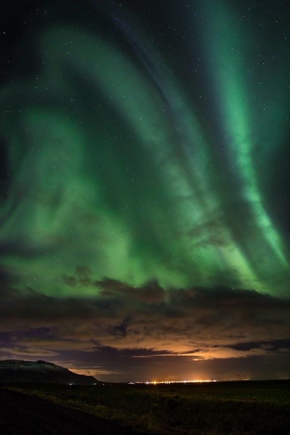 Northern Lights over Reykjavik. by Robert Williams