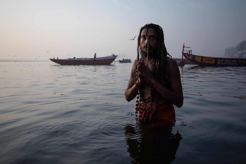 Holly man taking a dip in the Ganga by Gil Kreslavsky