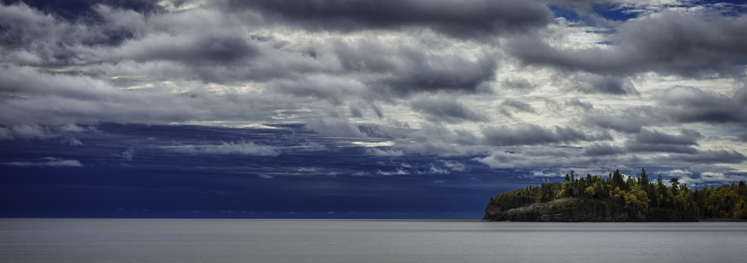 Moody Sky Over Lake and Island by Roger Applegate