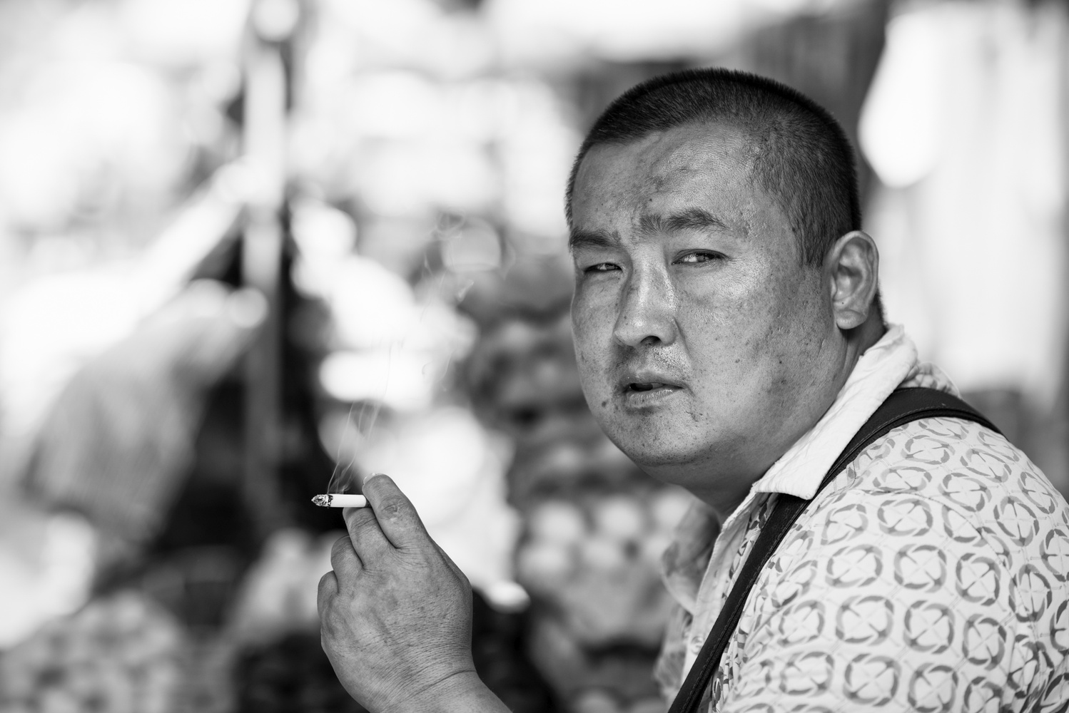A chinese man smoking in a street market in Xi'An by Léonard Rodriguez