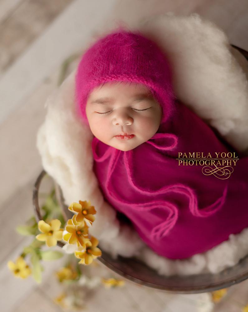 Newborn portrait with flowers by Pamela Yool