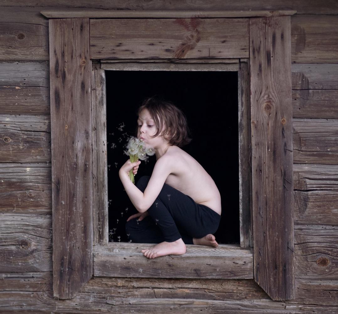 Kid, blowing dandelion by Judita Juknelė