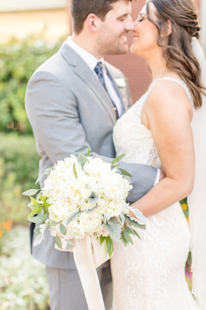 Romantic Bouquet shot of bride & groom kissing by Katie Dixon