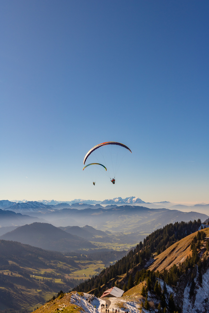 Paragliders flying straight to a valley by Vik Fuchs