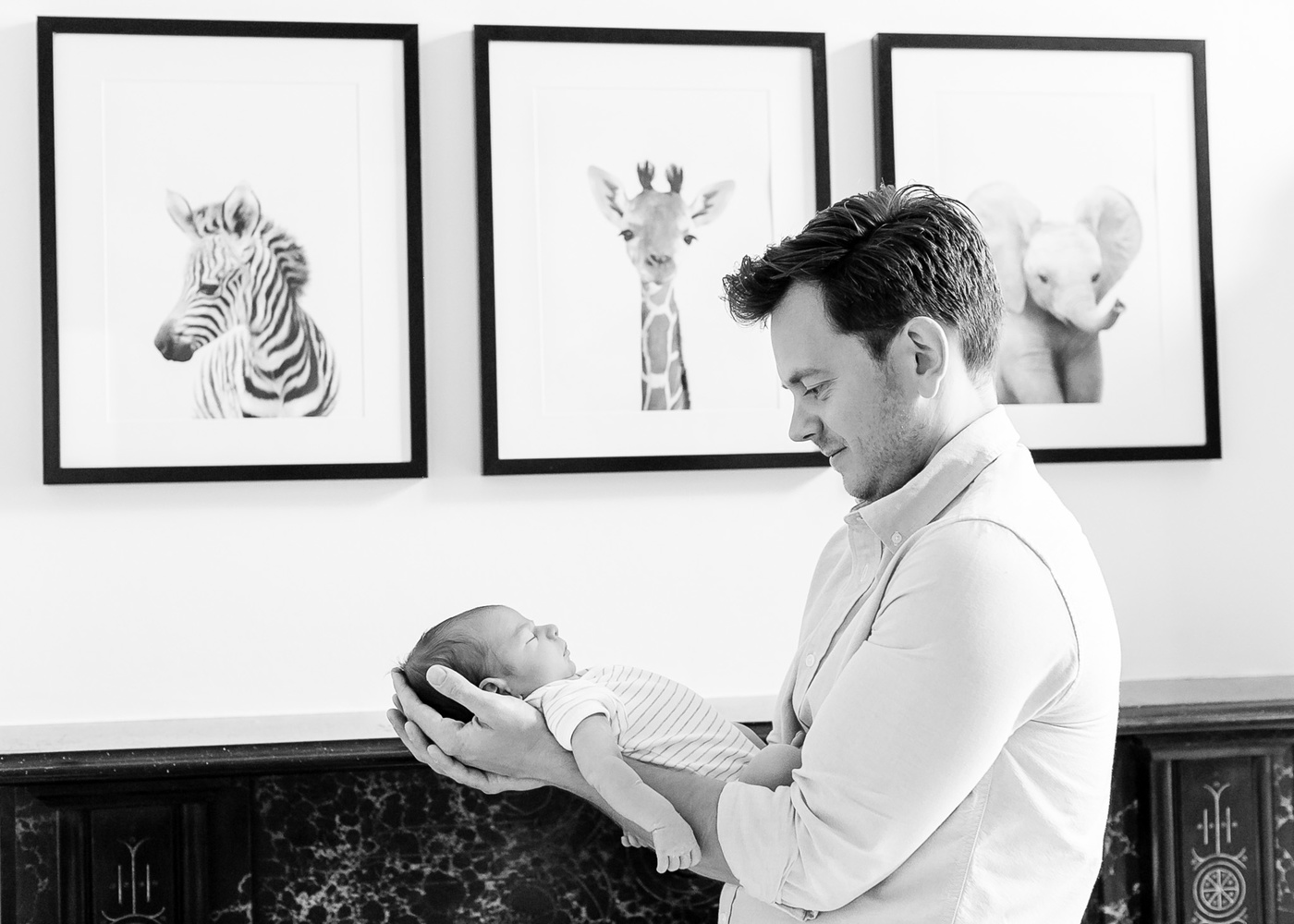 Father holding newborn in his arms by Louise Downham
