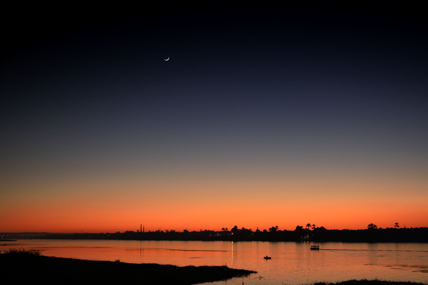 moon in the night sky over the last of a sunset by Simon Richards