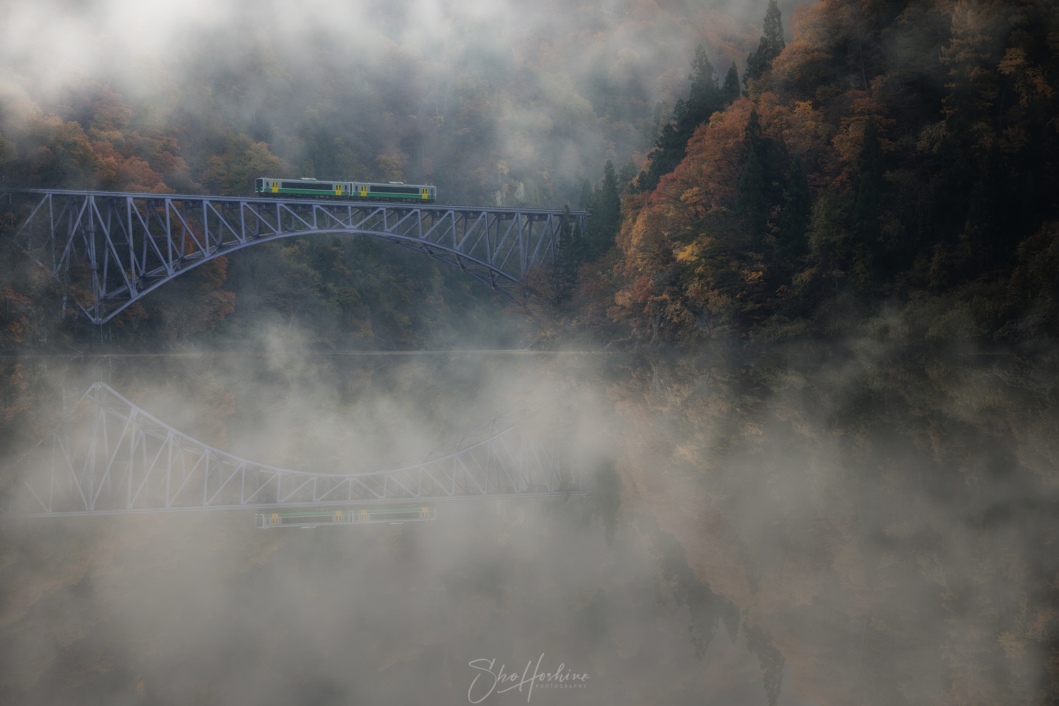 Train running in the river fog by Sho Hoshino