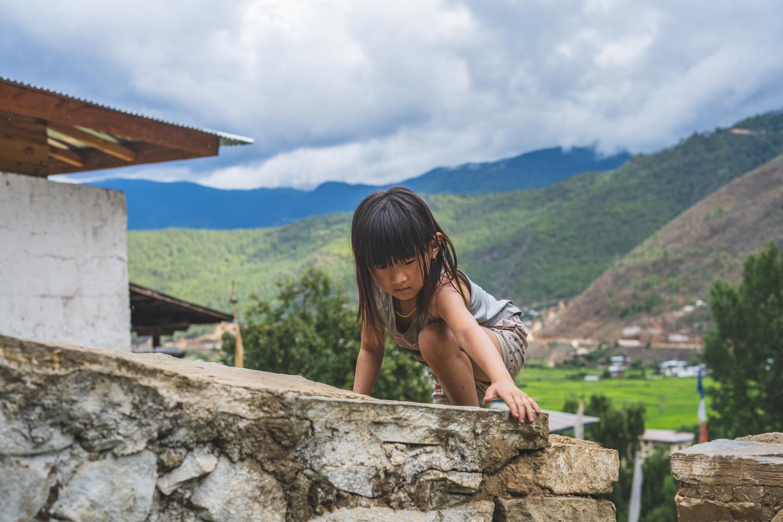 Strong girl child climbing a wall by Pragyan Bezbaruah