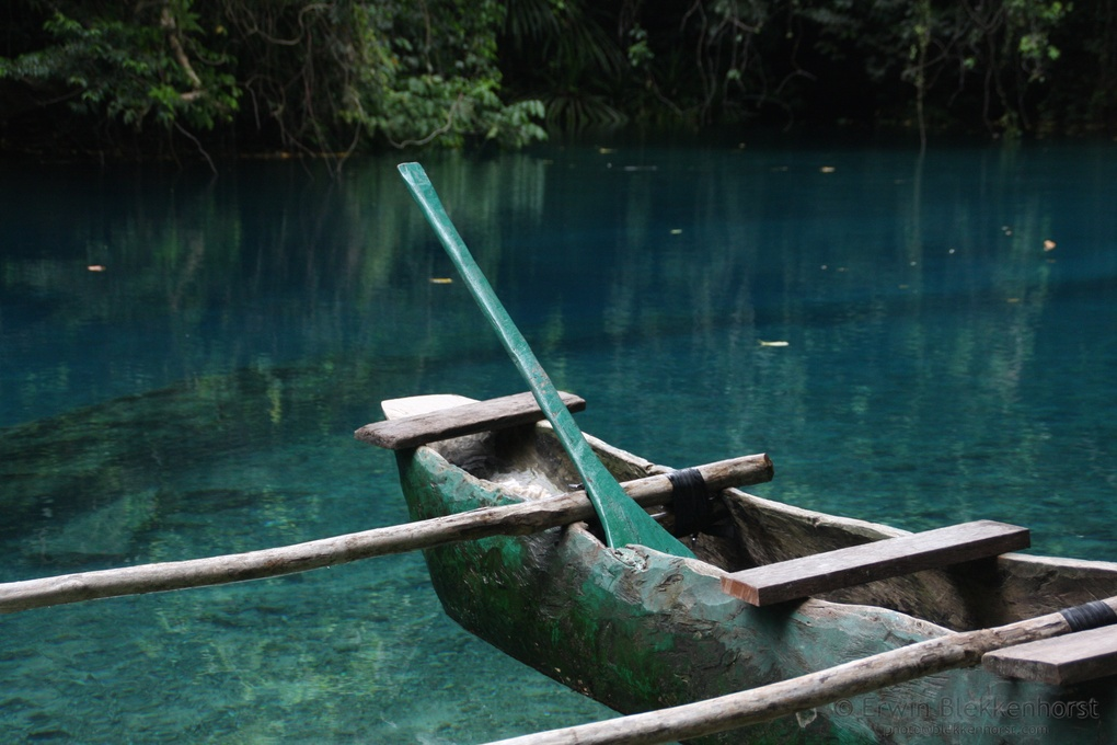 Outrigger canoe in clear water of Blue Hole by Erwin Blekkenhorst
