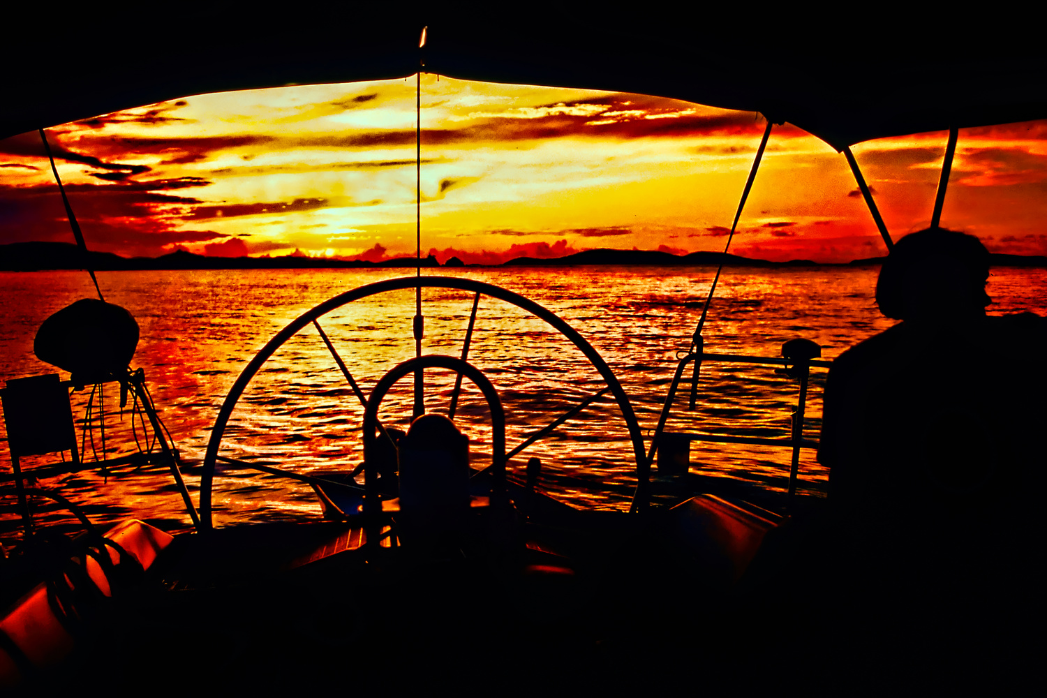 Sailing in the islands at sunset. by Bill Jonscher