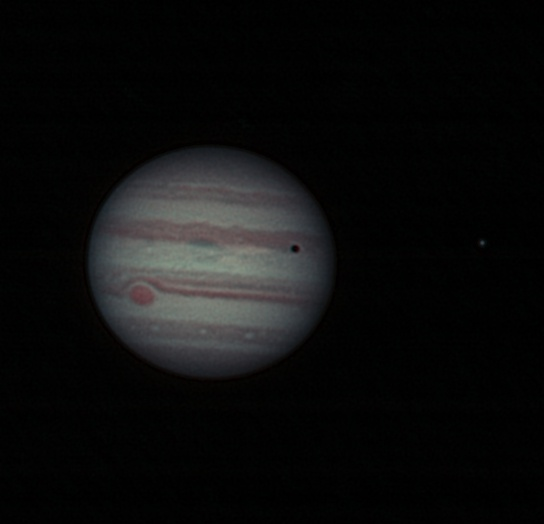 Jupiters Great red spot, and its moon Io casting a shadow on the gas giant. by Josh Borup