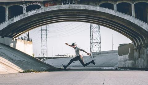 man taking long stride under urban overpass