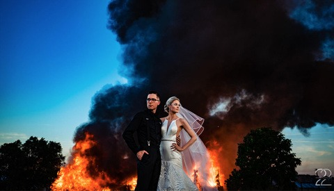 Photographer Shoots Bride and Groom's Wedding Pictures With a Burning Building as a Backdrop