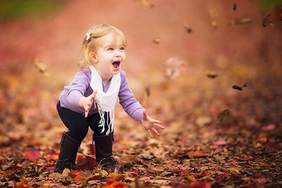 excited girl tossing leaves