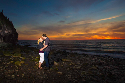 engaged couple embracing on rocky beach at sunset