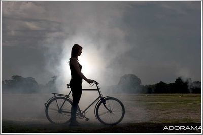 silhouette of girl standing beside bike