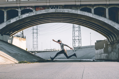 man taking long stride under urban overpass