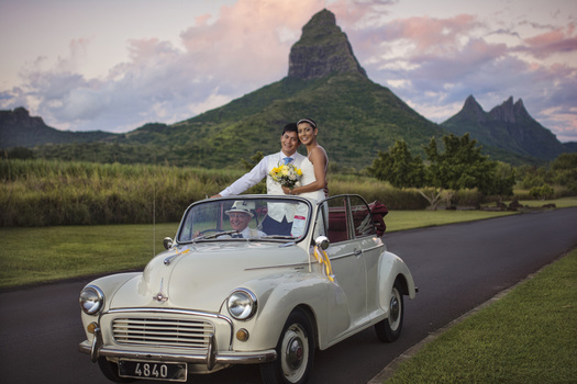 Couple in vintage car going to wedding with mountain and skies in the back