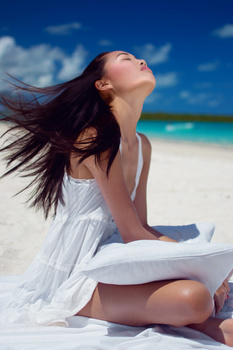 Girl waking up at the beach by the blue sky