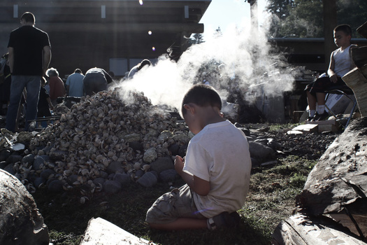 Young boy helps his tribe cook clams in the traditional way.