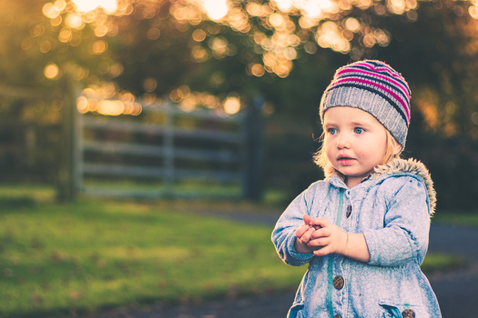 cute little girl. photograph of toddler. shallow depth of field. child portrait. outdoor portrait of little girl in warm coat.
