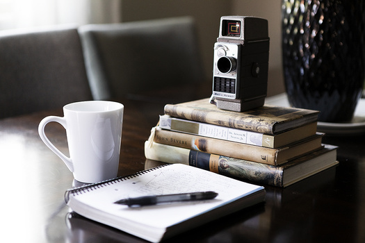 Notebook on desk with coffee and books