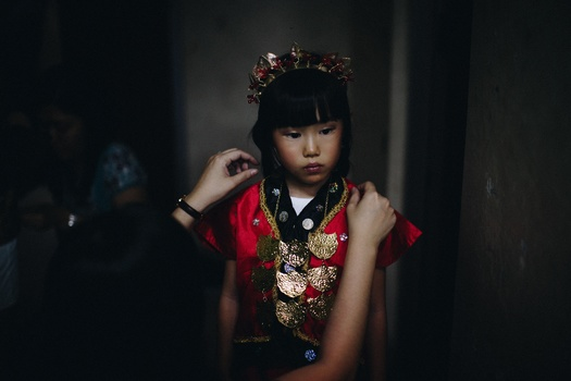 a small girl wearing a traditional Chinese dress