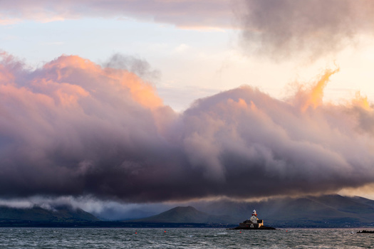 Photograph of a lighthouse under stormy skies during sunset