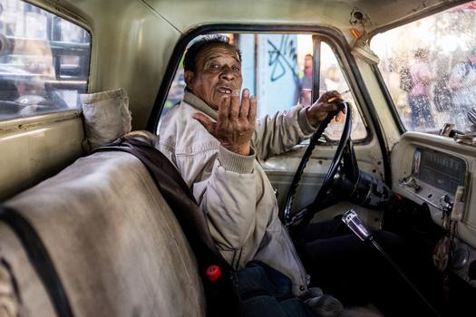 An older man in a vintage car