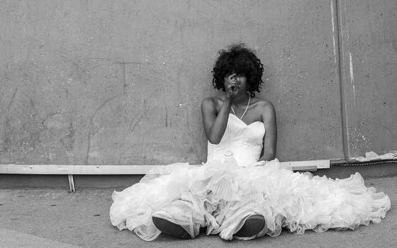 A young woman in a white dress sat on the street.
