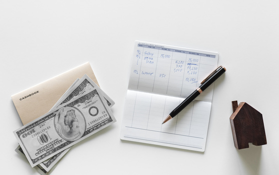 a stock photo of dollar bills, a check ledger and a home figurine