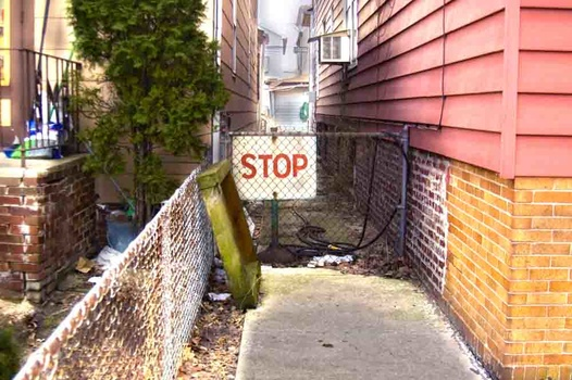 an HDR phot of a stop sign in an alley