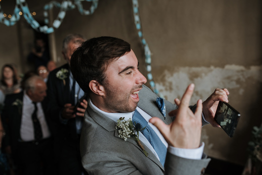 A groomsman taking a phone photograph of the couple