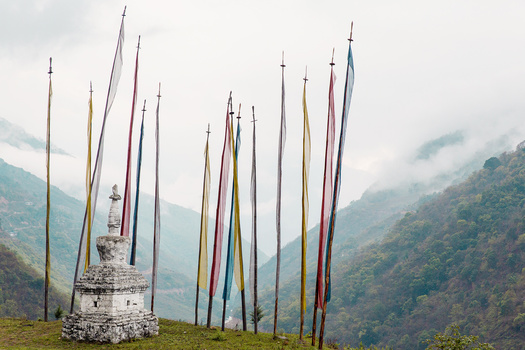 Prayer flags over a lush green valley