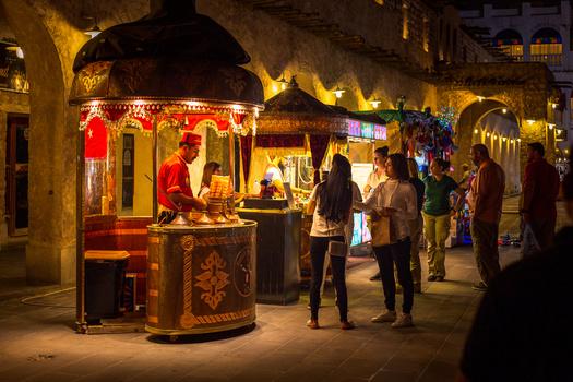 a Turkish ice-cream vendor at work in Doha, Qatar, at night.